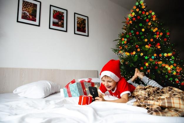 Chłopiec w czerwonych czapkach mikołaja patrzy na tablet i komunikuje się z dziadkami