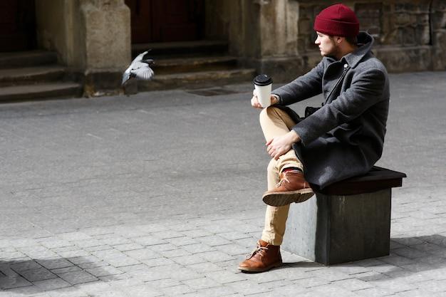 Chłopiec w czerwonym kapeluszu wygląda na gołębie latające wokół niego