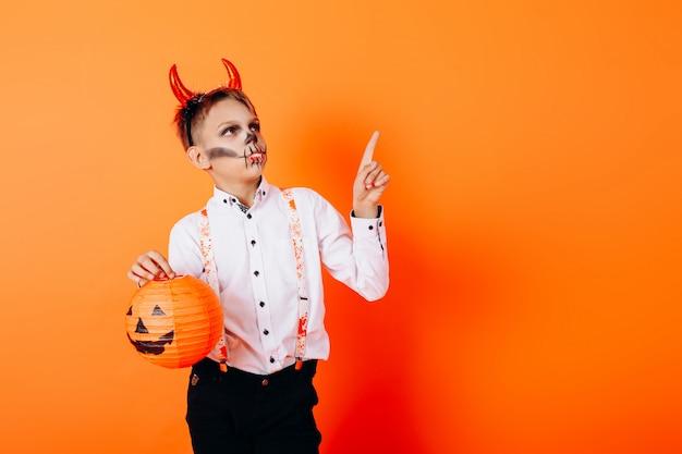 Chłopiec w diabelskim maskaradowym makijażu trzyma dyni i wskazuje w górę. halloween