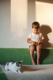 Chłopiec w domu je jagodę na kanapie w pobliżu kota zdrowy posiłek pozytywna osoba urocze zwierzę