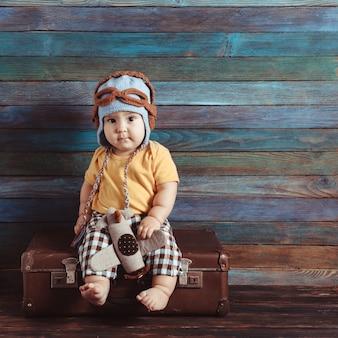 Chłopiec w dzianinowej czapce pilota bawi się samolocikiem, siedząc na staromodnej walizce