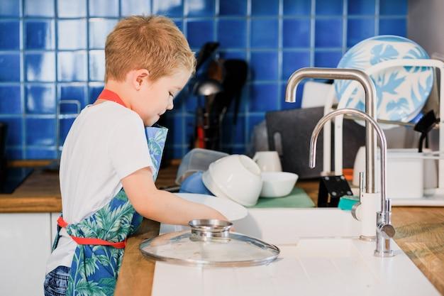 Chłopiec w fartuchu zmywa naczynia w domowej kuchni.