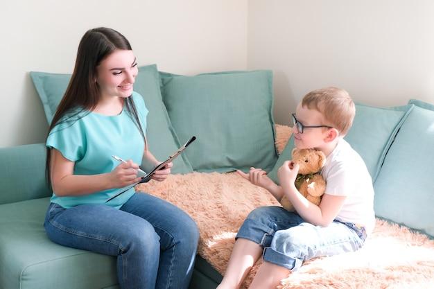 Chłopiec w gabinecie psychologa. psycholog rozmawia z dzieckiem, problemy studenckie. wsparcie emocjonalne