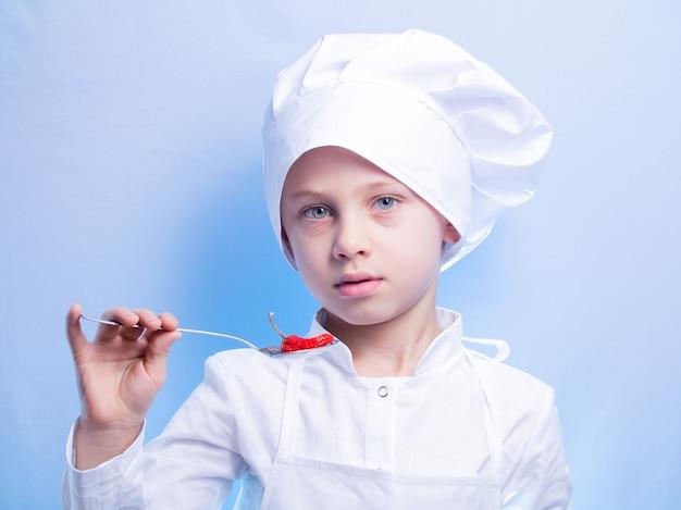 Chłopiec w garniturze i czapce kucharza uśmiecha się