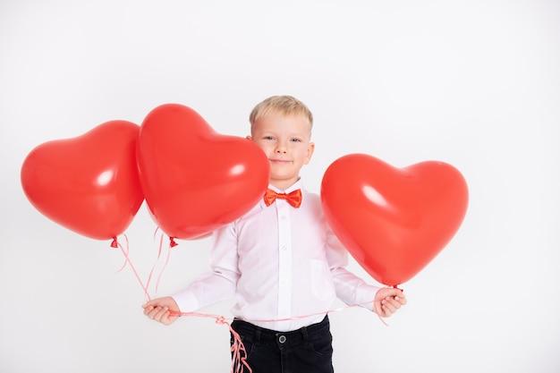 Chłopiec w garniturze i czerwonej muszce trzyma balony w kształcie serca