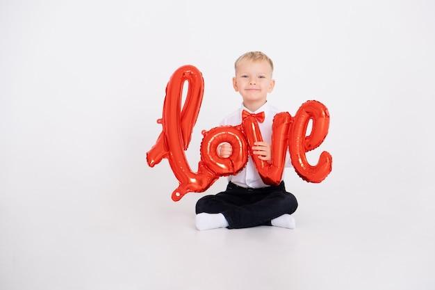 Chłopiec w garniturze i czerwonej muszce trzyma napis miłość z balonów na białym tle.