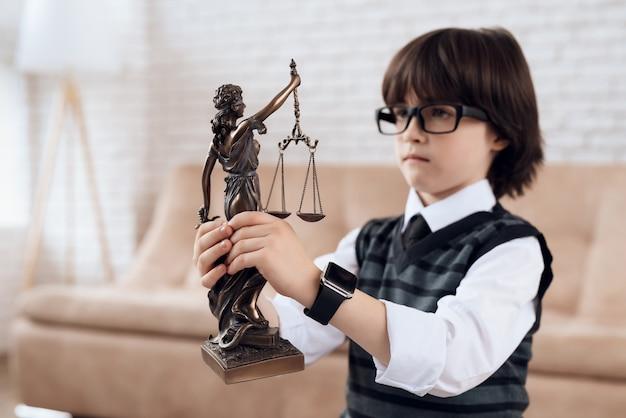 Chłopiec w garniturze i krawacie trzyma figurkę femidy.