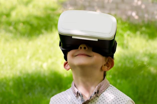 Chłopiec w hełm wirtualnej rzeczywistości na ścianie zielonej trawie