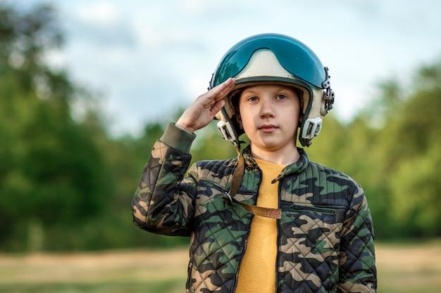 Chłopiec w hełmie pilota salutuje.
