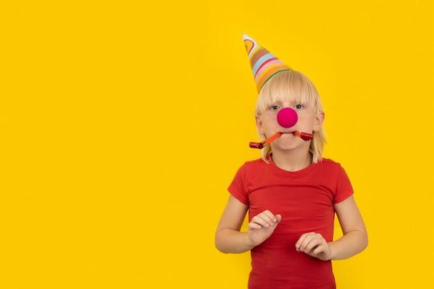 Chłopiec w imprezowym kapeluszu, nos klauna i gwizdek. impreza świąteczna dla dzieci.