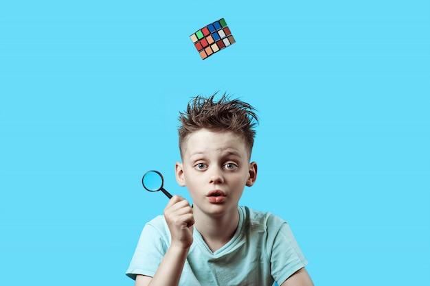Chłopiec w jasnej koszulce trzyma w ręku małe szkło powiększające, a kostka rubika spada z góry.