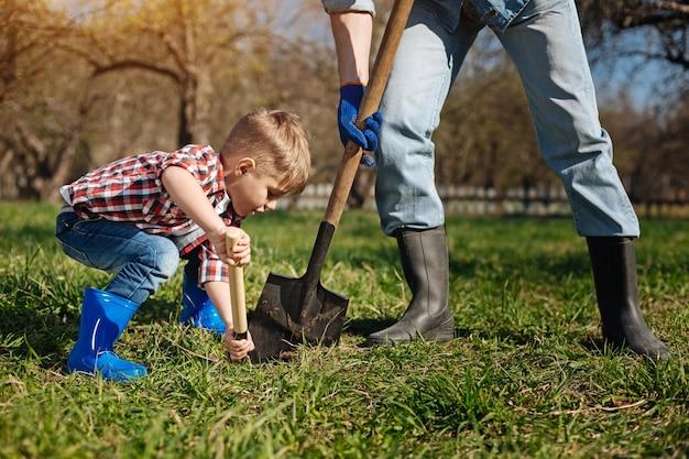 Chłopiec w jasnoniebieskich kaloszach pomaga swojemu dziadkowi zgarniać ziemię pod nowe drzewko owocowe