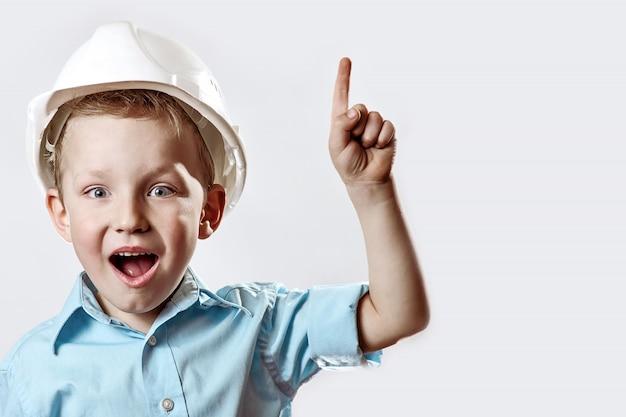 Chłopiec w jasnoniebieskiej koszuli i hełmie budowlanym brygadzisty podniósł palec