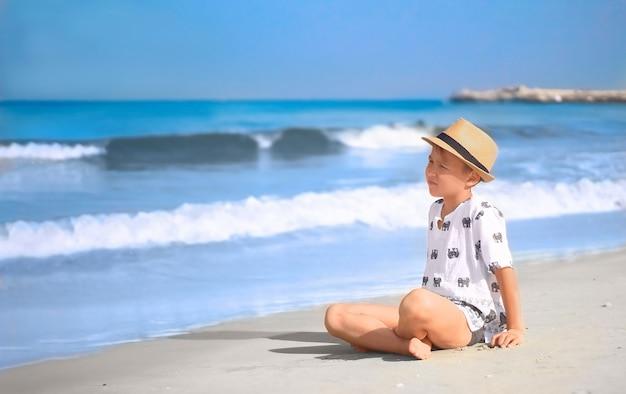 Chłopiec w kapeluszu siedzi na plaży o poranku, patrząc na fale