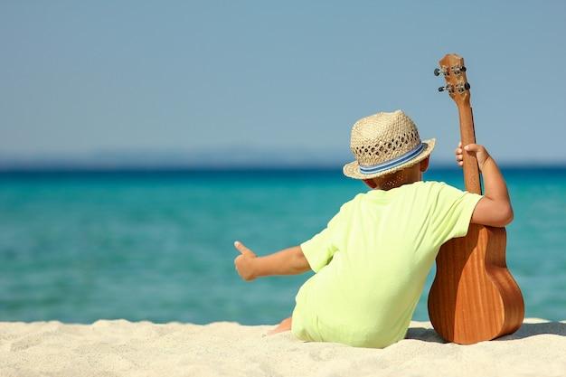 Chłopiec w kapeluszu siedzieć na plaży z ukulele latem w grecji