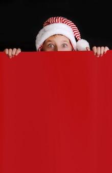 Chłopiec w kapeluszu świętego mikołaja, trzymając czerwony pusty sztandar na życzenia świąteczne. pojedynczo na czarno
