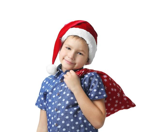 Chłopiec w kapeluszu świętego mikołaja z torbą pełną prezentów na białym tle, zbliżenie