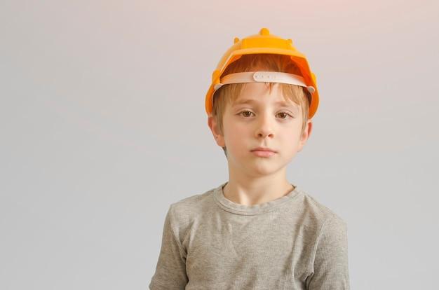 Chłopiec w kasku budowniczego i okulary. izolować