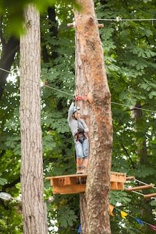 Chłopiec w kasku i sprzęt bezpieczeństwa w parku linowym na tle przyrody