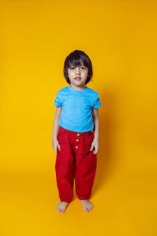 Chłopiec w kolorowych ubraniach, czerwone spodnie i niebieska koszulka, stoi na żółtej ścianie