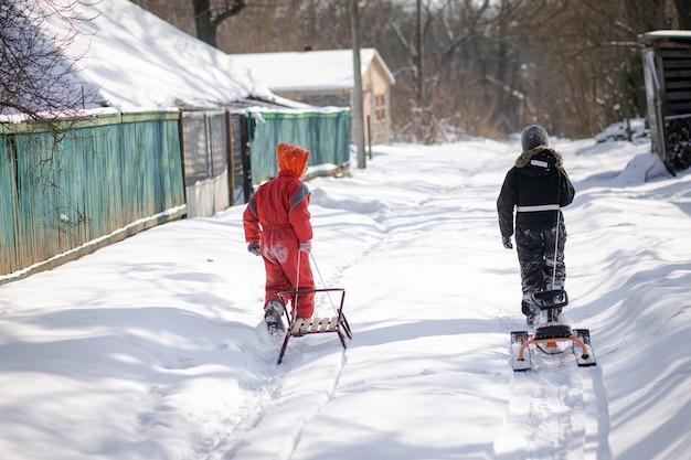 Chłopiec w kombinezonie narciarskim na śniegu z sankami. dziecko jedzie na hulajnodze. aktywne gry na ulicy. zdrowy tryb życia