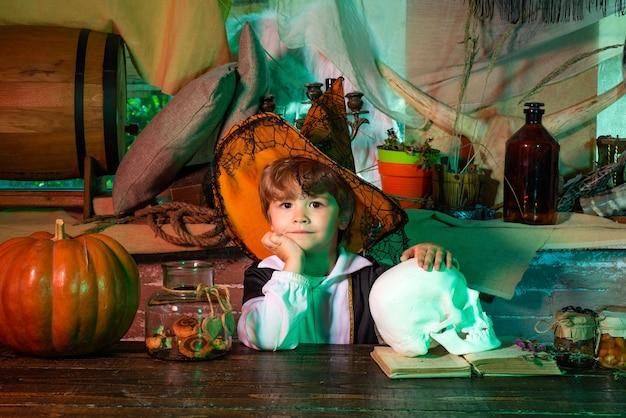 Chłopiec w kostiumie na halloween z dynią stary drewniany dom wesołego halloween śliczny mały chłopiec...