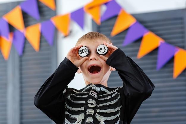 Chłopiec w kostiumie szkieleta wygłupia się i bawi ciasteczkami