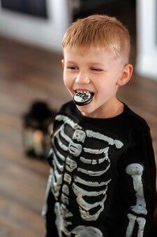 Chłopiec w kostiumie szkieleta wygłupia się i śmiało gryzie przerażające ciasteczko