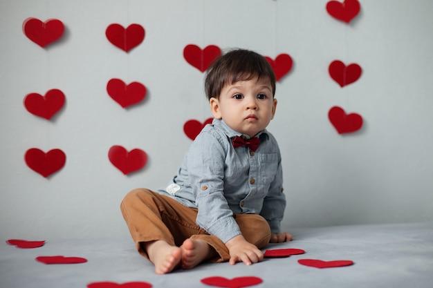 Chłopiec w koszuli z czerwoną muszką siedzi na szarej ścianie z sercami w walentynki.