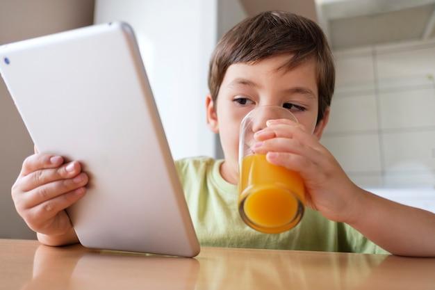 Chłopiec w kuchni pije sok pomarańczowy i ogląda wideo na tablecie