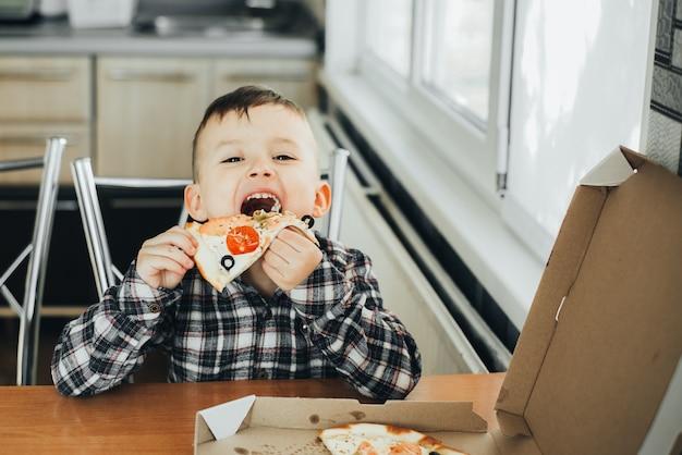 Chłopiec w kuchni w domu je pizzę z łososiem