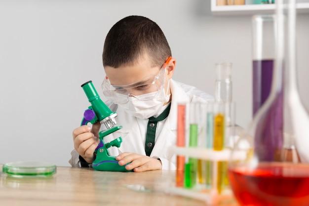 Chłopiec w laboratorium z mikroskopem