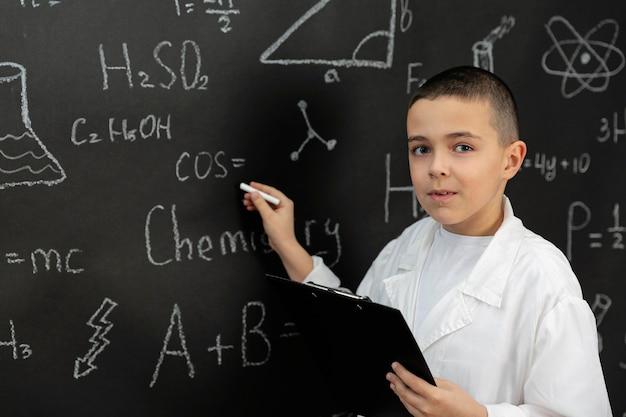 Chłopiec w laboratorium z pisaniem na płaszczu