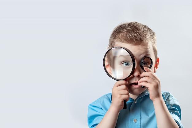 Chłopiec w lekkiej koszulce patrząc na duże szkło powiększające