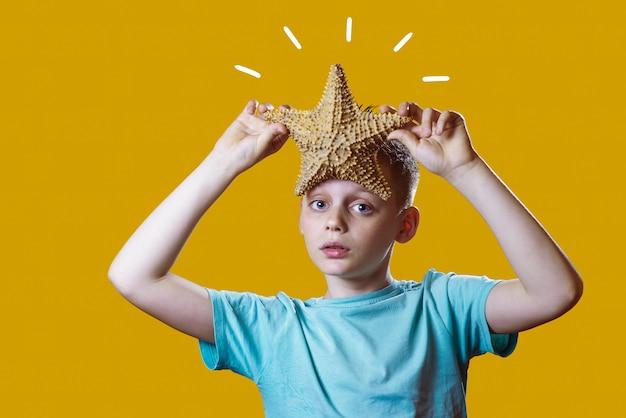 Chłopiec w lekkiej koszulce trzyma rozgwiazdy na żółtym tle