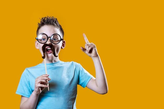 Chłopiec w lekkiej koszulce z wąsami i okularami trzyma palec wskazujący na pomarańczowo
