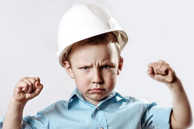 Chłopiec w lekkiej koszuli i kasku budowniczy pokazuje, jak jest silny i pewny siebie
