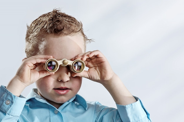 Chłopiec w lekkiej koszuli, patrząc przez lornetki na światło