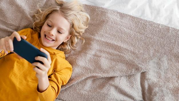Chłopiec w łóżku, grając na telefonie komórkowym