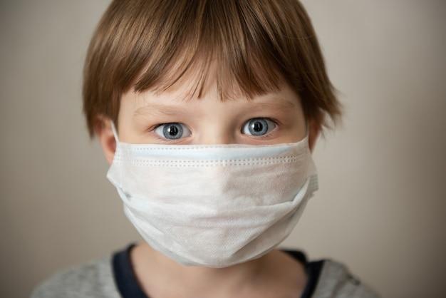 Chłopiec w masce medycznej. blokada koronawirusa covid-19, panika. szczepionka przed nowym wirusem. negatywne emocje
