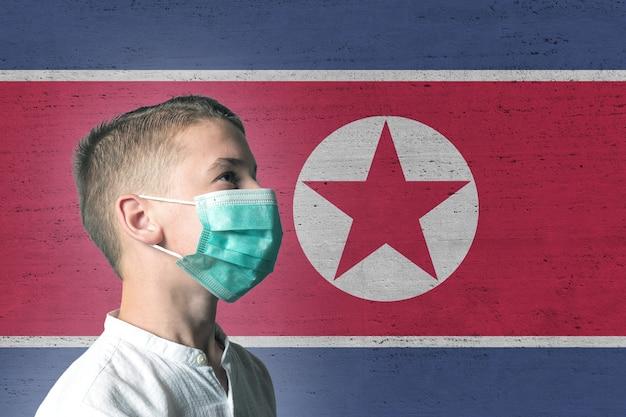Chłopiec w masce medycznej na twarzy na tle flagi korei północnej.