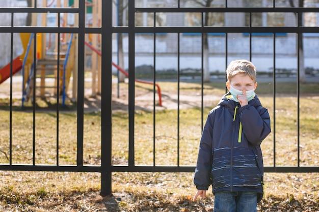 Chłopiec w masce medycznej wykonuje gest shhh