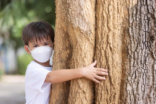 Chłopiec w masce stoi przytulając się do wielkiego drzewa i patrząc na kamerę. problem z zanieczyszczeniem.