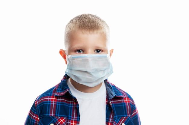 Chłopiec w masce. uczeń w koszuli. zbliżenie. środki ostrożności podczas pandemii koronawirusa. odosobniony.