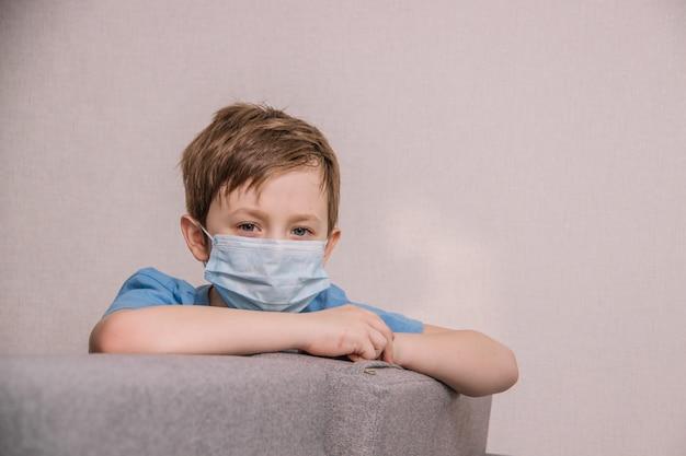 Chłopiec w medycznej masce siedzi na kanapie i jest smutny
