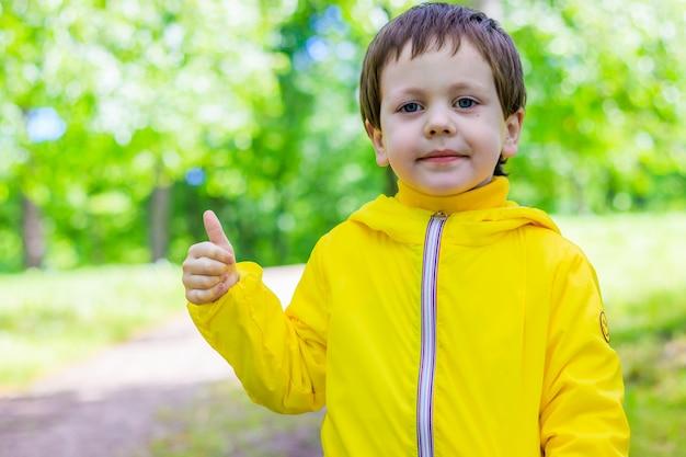 Chłopiec w naturze na sobie żółtą kurtkę z kciukiem do góry