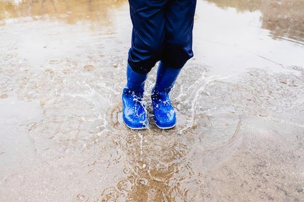 Chłopiec w niebieskich butach z wodą skacze w kałuży.