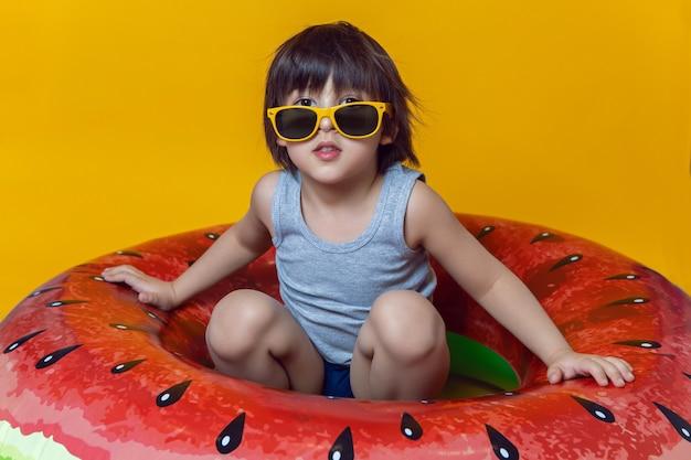 Chłopiec w niebieskich kąpielówkach i okularach przeciwsłonecznych leżący na nadmuchiwanym kółku w kształcie arbuza na żółtej ścianie