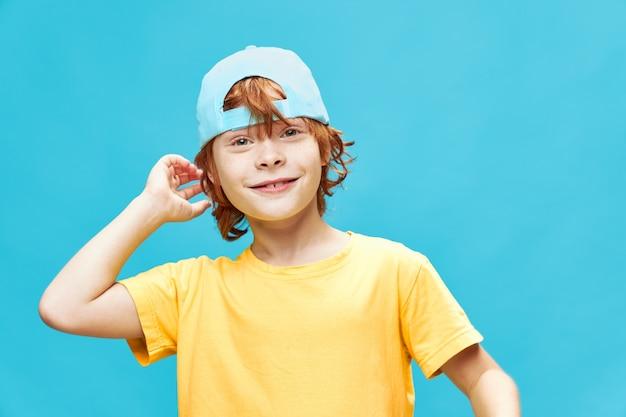 Chłopiec w niebieskiej czapce na białym tle rude włosy żółta koszulka