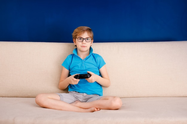 Chłopiec w niebieskiej koszulce i dużych okularach siedzi na kanapie i gra w domu z gamepadem. niebieskie tło i wolne miejsce na tekst